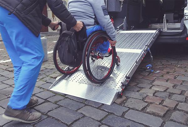 Ein Rollstuhlfahrer wird in einen Wagen über eine Rampe geschoben.