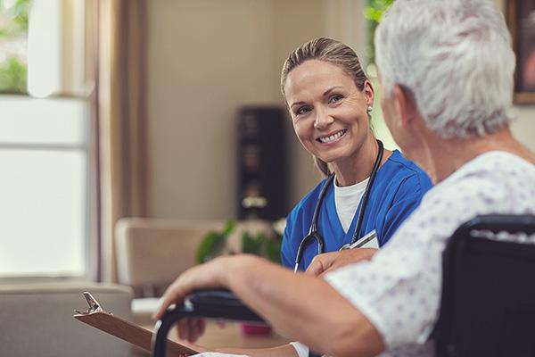 Eine Pflegerin spricht mit einer Seniorin.