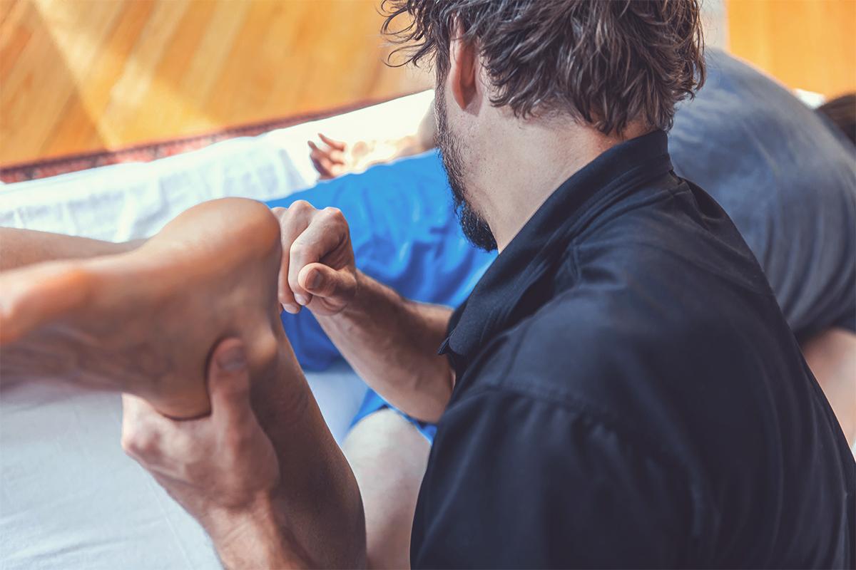 Massagebehandlung auf der Liege durch einen Therapeut.