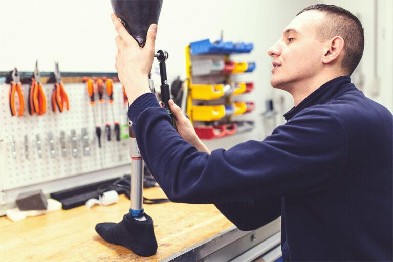 Ein Orthopädietechniker fertigt eine Beinprothese in der Werkstatt an.
