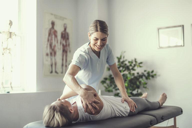 Eine Physiotherapeutin behandelt eine junge Patientin auf der Liege.