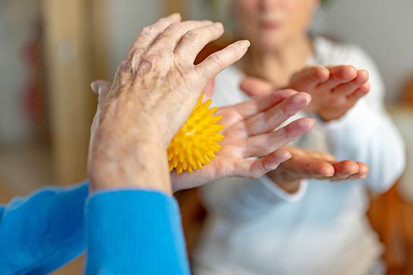 Eine Rentnerin macht Lockerungsübungen mit einem Igelball