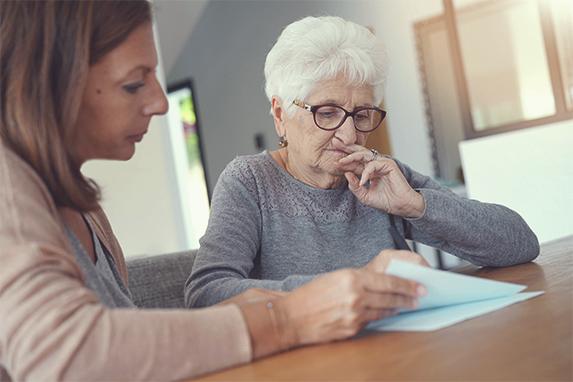 Eine Frau berät eine ältere Dame bei der Sichtung von Dokumenten.