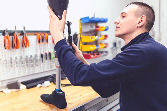 Ein junger Mann arbeitet an einer Beinprothese in einer Werkstatt.