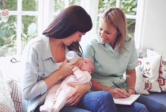 Eine Hebamme besucht eine junge Mutter und ihr Baby, dem die Flasche gegeben wird.