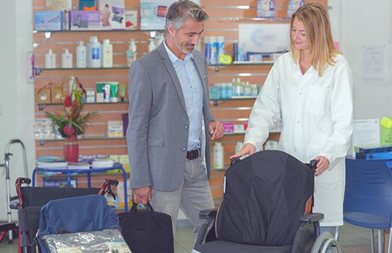 Eine Mitarbeiterin im Sanitätshaus zeigt einem Kunden einen Rollstuhl.