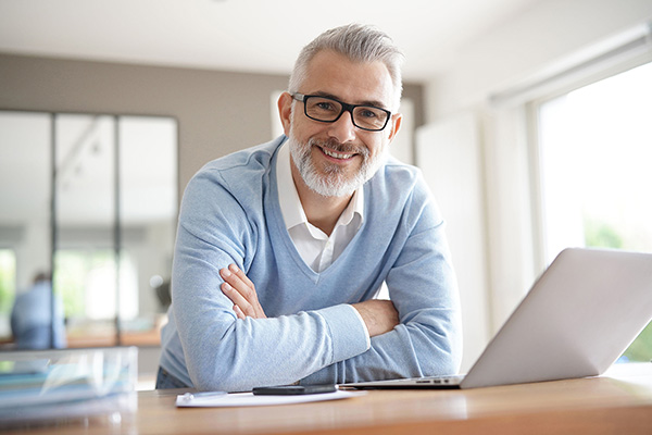 Älterer Mann sitzt lächelnd am Schreibtisch mit einem Notebook.