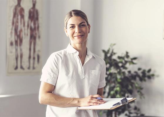 Eine Physiotherapeutin steht in ihrer Praxis mit Unterlagen in der Hand.